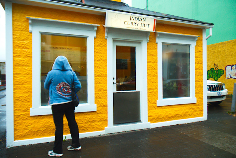 Pixie at Akureyri, standing before the smallest Indian restaurant I've seen