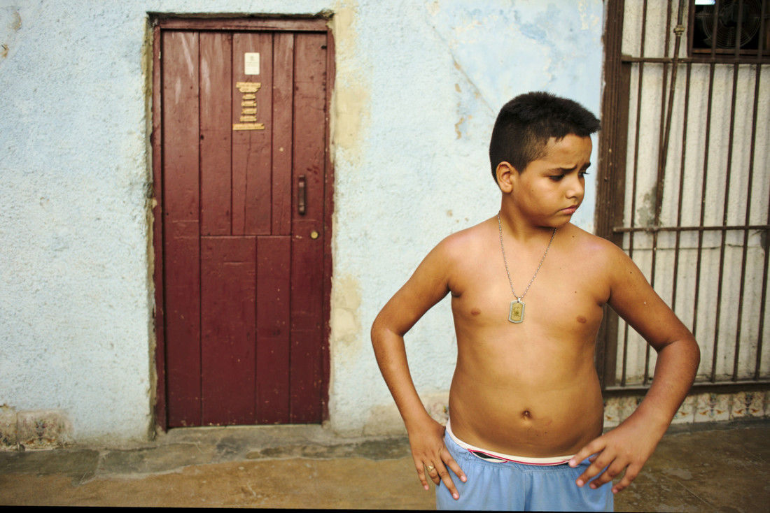 Boy playing in a pateo inside a solar at Centro Habana