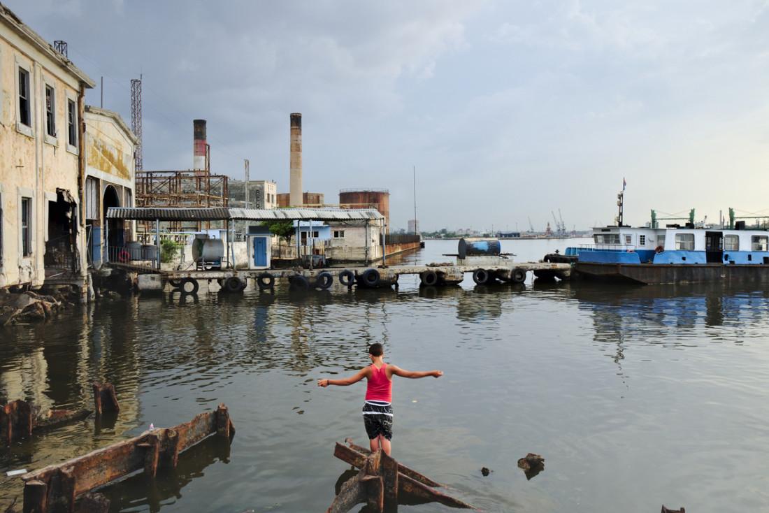 Boys fishing in the waters of the Havana bay, at Regla