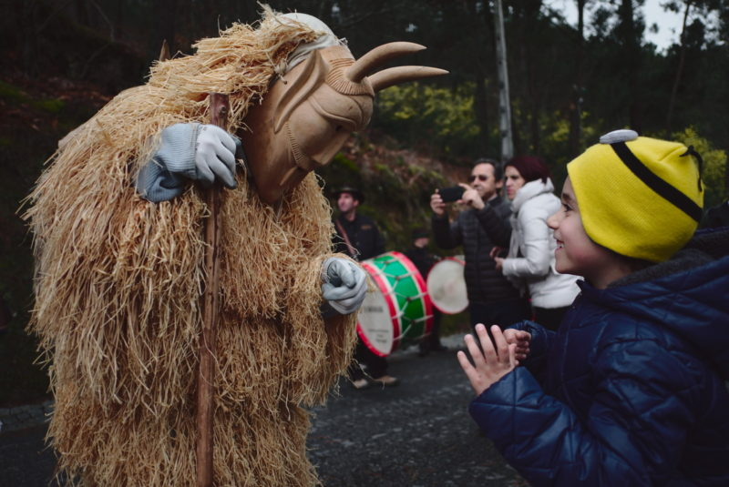 Shrovetide parade, little boy delighted with one of the caretos.